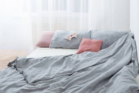 bed with gray linens and sleep mask   in white interior