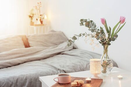 interior of bedroom with flowers, candles and cup of tea