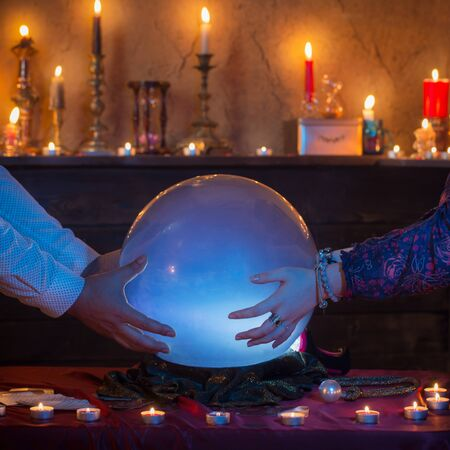 four hands of fortune teller with illuminated crystal ball Banque d'images