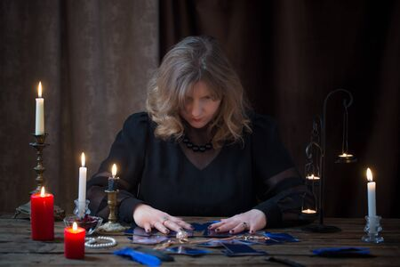 mature woman guessing with cards on dark background Reklamní fotografie
