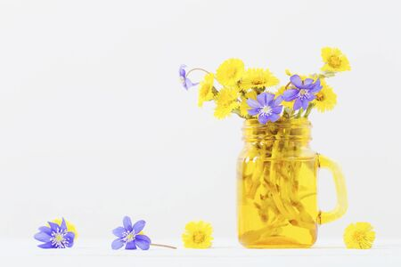 spring flowers in yellow jar on white background