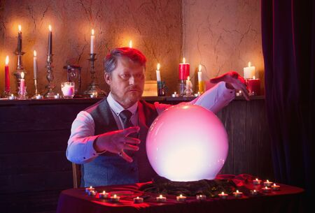man fortune teller with illuminated crystal ball
