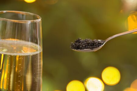 black caviar in  spoon and  glass of champagne