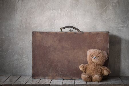 brouwn teddy bear and old suitcase on  grunge background