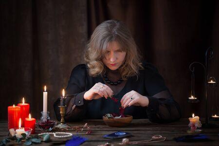 woman preparing  magic potion from dried herbs