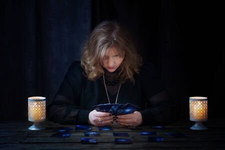 mature woman guessing with cards on dark background