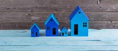 blue paper houses stands over  wooden background