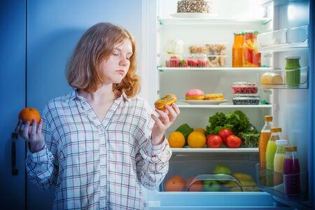 teenager girl at fridge with food