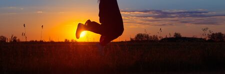 jumping girl in field at sunset