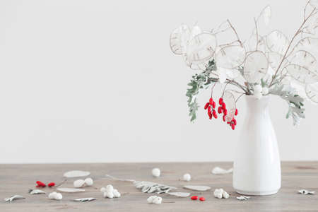 bouquet with lunaria and red berries in white vase on wooden table Stock fotó