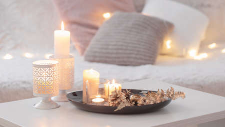 Christmas decoration with burning candles on white table against the background of sofa with plaids and pillows. Cozy home and holiday concept Stock fotó