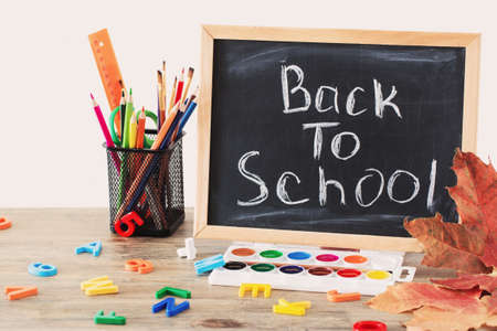 chalkboard with text and school supplies on wooden table, back to school concept Stock fotó