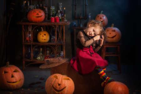 little witch with halloween pumpkins indoor