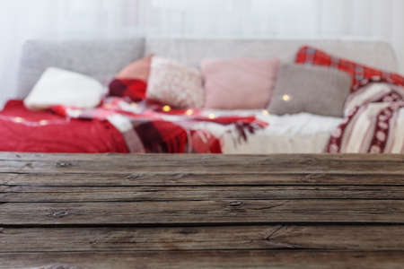 old wooden table on background sofa with pillows and plaids