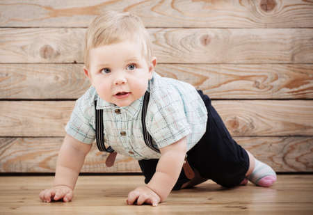 baby in shirt and suspenders shorts on wooden background