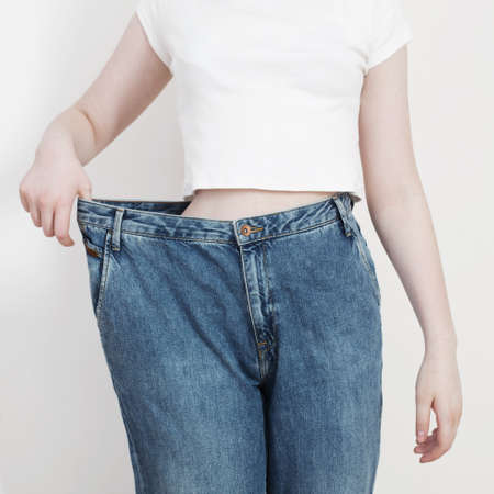 girl pulling her big jeans and showing weight loss