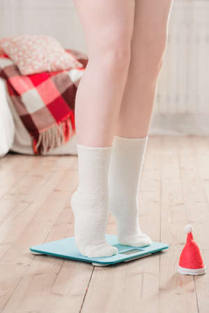 Female feet standing on blue electronic scales for weight control with Christmas santa hat on wooden floor