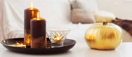 home decor with golden pumpkin and burning candles Foto de archivo