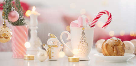 cocoa with marshmallow and christmas decor in pink and gold colors