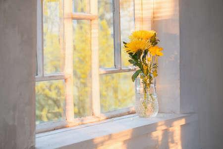yellow flowers in vase on windowsill Foto de archivo