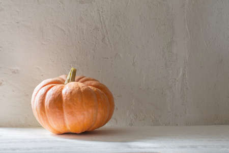 orange pumpkin on wooden table on background white wall Foto de archivo - 155425056
