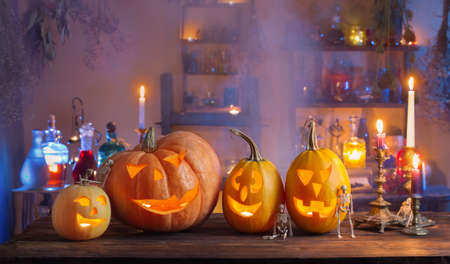 Halloween pumpkins with candles and magic potions at night indoor Foto de archivo - 155513290