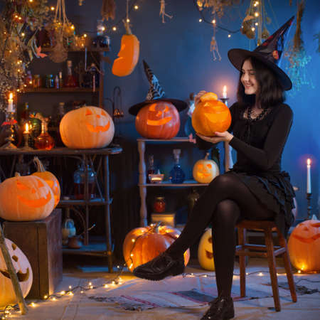teenage girl dressed as a witch with pumpkins on the background of decor for Halloween