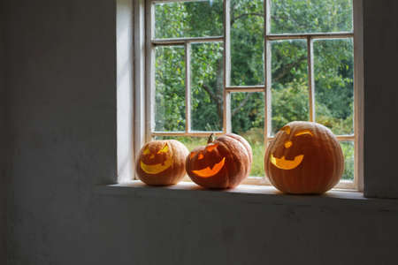Halloween pumpkins on white windowsill Foto de archivo