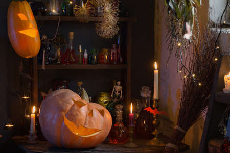 Halloween pumpkins with lights and burning candles and magic potions in witch's house