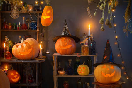 Halloween pumpkins with lights and burning candles and magic potions in witch's house Imagens