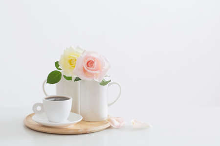 two roses in cups with cup of coffee