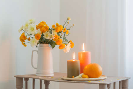 autumn flowers with burning candles and pumpkins on vintage wooden shelf