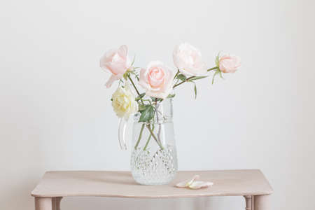 beautiful roses in glass jug on white background