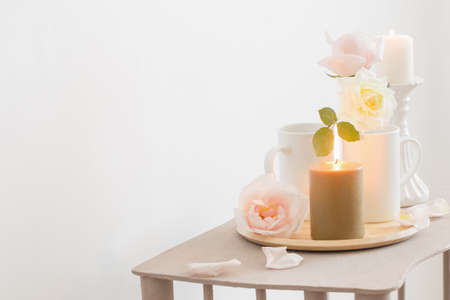 beautiful roses and burning candles on white background