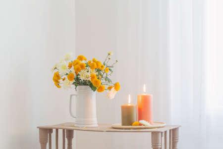 autumn flowers with burning candles on vintage wooden shelf Standard-Bild