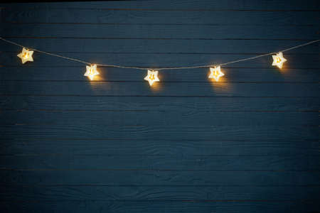 Christmas lights on blue wooden background Foto de archivo