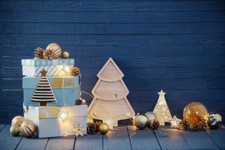 Christmas gifts with golden decorations on blue wooden background