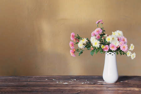 chrysanthemums in vase on old wooden table