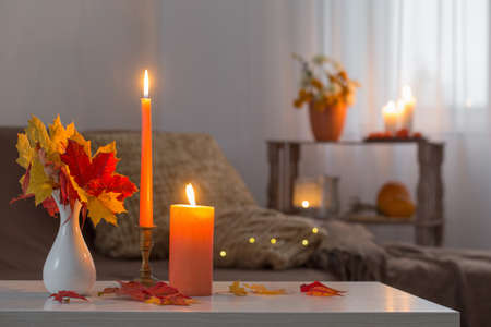 burning candles with autumn decor on white table at home Foto de archivo