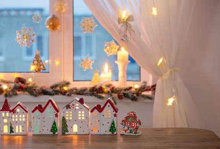 Christmas toy houses on background of decorated window Banque d'images