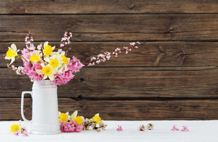 spring flowers in white jug on wooden background