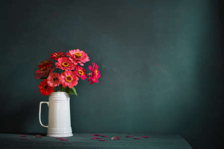 pink flowers in white jug on dark green background
