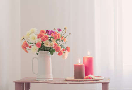 flowers with burning candles on vintage wooden shelf