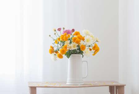 chrysanthemum flowers in white jug in white interior