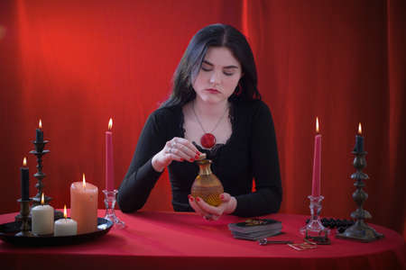 young witch holding vial with magic potion on red background Standard-Bild