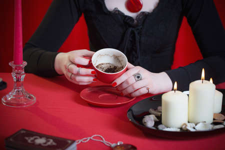 young girl in a black dress is engaged in fortune telling on coffee grounds on red background 版權商用圖片