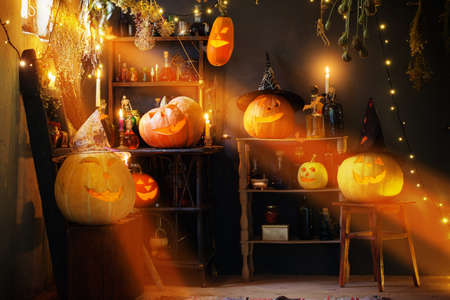 Halloween pumpkins with lights and burning candles and magic potions in witch's house Foto de archivo