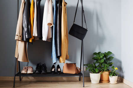 basic women's autumn wardrobe with shoes and handbags on hanger