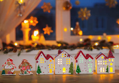 Christmas toy houses on background of decorated window Zdjęcie Seryjne