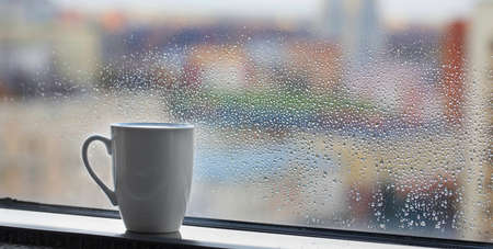 cup of coffee on windowsill with raindrops on glass